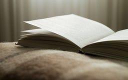 Open boek op een deken, op tegenover het venster Stock Afbeeldingen