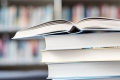 Open boek op een stapel boeken op een lijst stock afbeeldingen