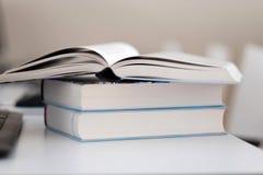 Open boek op een stapel boeken op een lijst stock afbeelding