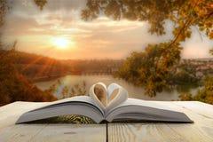Open boek op houten lijst aangaande natuurlijke vage achtergrond Stock Afbeelding