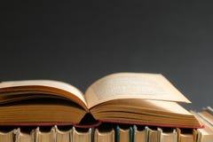 Open boek op zwarte achtergrond, boek met harde kaftboeken op houten lijst e stock foto