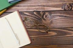 Open boek, pen en glazen op een houten lijst stock fotografie