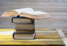 Open boek, stapel boek met harde kaftboeken op houten lijst Stock Foto