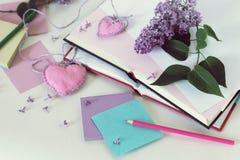 Open boeken, referentiesharten, document, potloden, takken van lilac bloemen op de lijst stock foto's