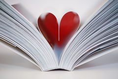 Open Book. Pages of a book folded into a heart shape. Symbolizes a love of books, reading and education, or romance stock photography