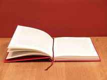 Open book. Open red book on wooden table against red wall Royalty Free Stock Photo
