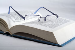 Open book. Glasses on the book on the white background Stock Images