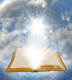 Open book. A golden mytsical book lies open with stars rising from the covers with a cloudy sky as a background.  Concept for new age or spiritual meaning Royalty Free Stock Photos