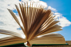Open book against a clear sky closeup Stock Photos