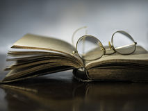 Open book with antique reading glasses Stock Photography