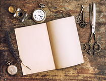 Open book and antique writing tools. Vintage style. Open diary book and antique writing tools on wooden background. Vintage style toned picture stock image