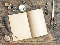Open book and antique writing tools vintage. Open book and antique writing tools on wooden background. Vintage style toned picture royalty free stock photos