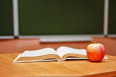 Open book and an apple on the desk in the classroom. School. Stock Photography