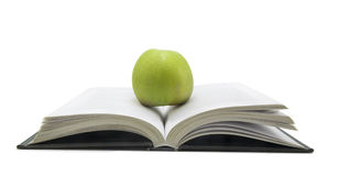 Open book with apple on it isolated on white background Stock Photo