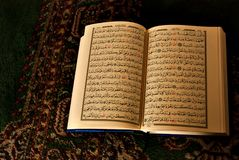 Open book in arabic writting. Opened quran wirttin in arabic, on an oriental carpet with dusk lighting Royalty Free Stock Images