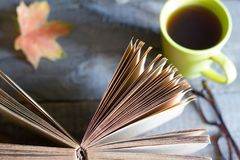 Open book autumn leaves tea and glasses abstract background on wooden boards stock photo