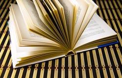 An open book on a bamboo mat Stock Images