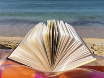 Open book at the beach. Book open at the beach as a concept of reading during summer Stock Images