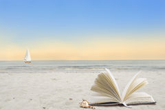 Open book on beach by sea Royalty Free Stock Photography