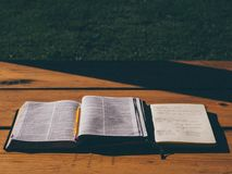 Open Book Bible on Brown Wooden Table Stock Photo