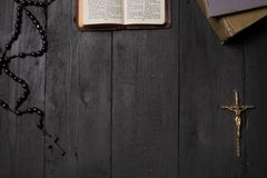 Open book of Bible and crucifix on dark table, top view