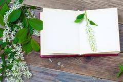 Open book with bird-cherry branches stock photos