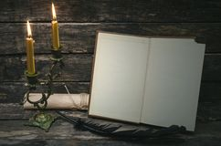 Open book with blank pages. Open book with blank empty pages in the light of burning candle. Writer or author concept royalty free stock photos
