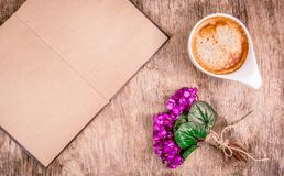 Open book with blank pages, spring flowers and cup of coffee. Coffee and violets on wooden background. Romantic concept. Copy space Royalty Free Stock Photography