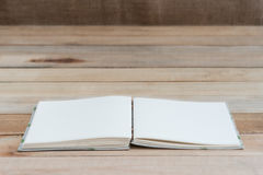 Open book with blank pages on wood table Stock Images