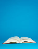 Open book on a blue background Stock Photo