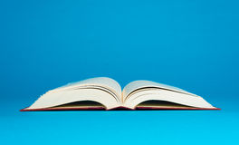 Open book on a blue background Royalty Free Stock Photography