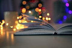 Book and blurred Christmas tree on background royalty free stock photography