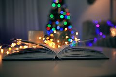 Open book and blurred Christmas tree royalty free stock photos