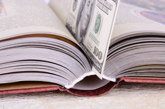 Open book with a bookmark $ 100. Open book with a brown cover closeup. bank note is $ 100 as a bookmark in a book. Photography executed in brown, beige, light Stock Images