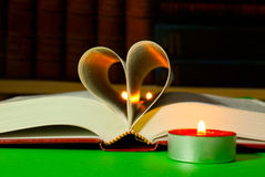 Open book with burning candle Royalty Free Stock Image