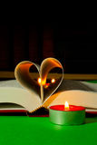 Open book with burning candle Royalty Free Stock Images