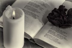 An open book with a candle. on the pages is a Bud of dried rose. stock images