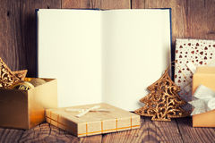 Open book with christmas decoration. On wooden background Stock Photos