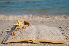 Open book sand seashells sea star beach sea shore blue sky white wave summer weekend vacation Royalty Free Stock Images