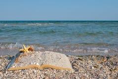Open book sand seashells sea star beach sea shore blue sky white wave summer weekend vacation Royalty Free Stock Photos
