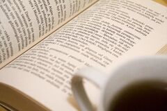 Open book and coffee cup Stock Images