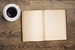 Open book and coffee cup top view on table Royalty Free Stock Images