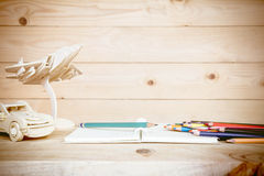 Open book and Colored pencils on wooden table. Royalty Free Stock Images