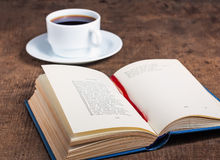 Open book and a cup of coffee on wooden surface Stock Photography