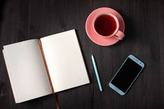 Open book, cup of tea, pen, phone on a black background stock photos