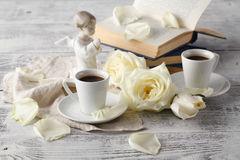 Open book and cup of tea on wooden table Stock Images