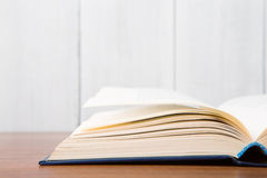 Open book on the desk over wooden background Royalty Free Stock Photos