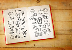 Open book with doodles over wooden table Stock Photos