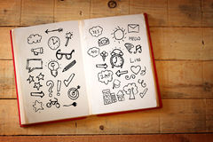 Open book with doodles over wooden table Stock Photo