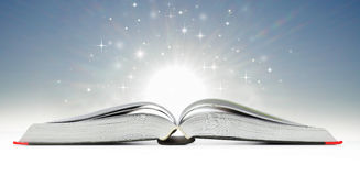 Open book emitting sparkling light Royalty Free Stock Photos